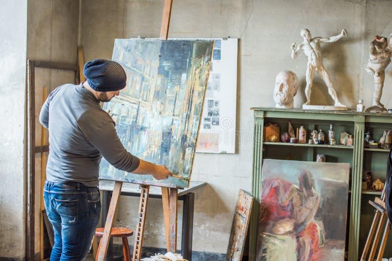 Konstnär i hans studiomålning med olje- färg arkivfoto