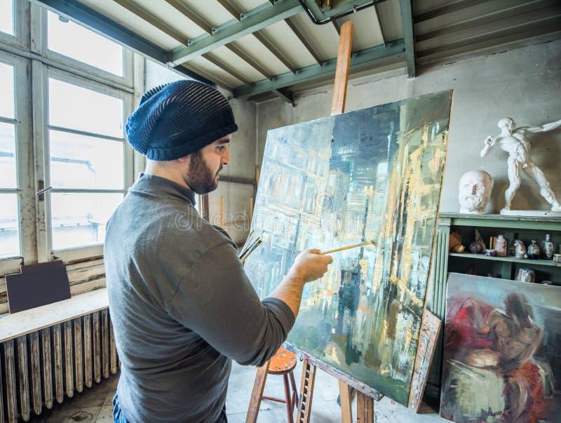 Konstnär/lärare som målar ett konstverk för en strid i hans studio royaltyfria foton