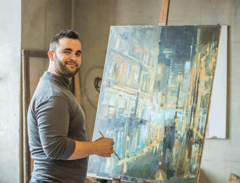 Konstnär/lärare som målar ett konstverk och le arkivbild