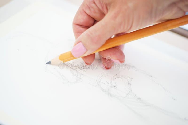 Konstnär med en blyertspennanärbild, medan dra en skissa på rengöringpapper royaltyfria bilder