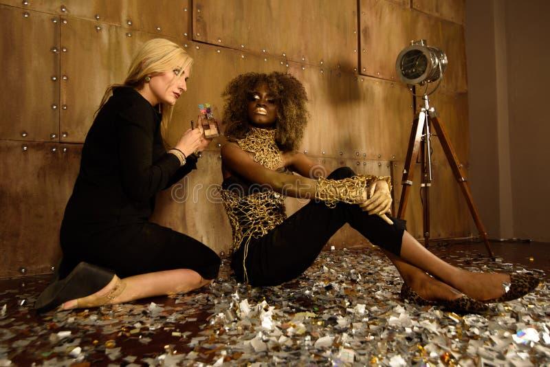 Konstnär som applicerar makeup till den härliga afrikansk amerikanmodellen på fotoforsen på golv i ljus guld- studio arkivbilder