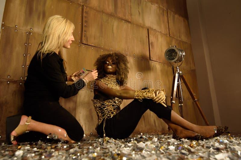 Konstnär som applicerar makeup till modellen på fotoforsen på golv i ljus guld- studio royaltyfri foto
