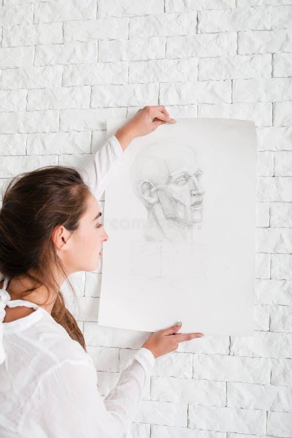 Konstnär som hänger hennes blyertspennastående på väggen royaltyfri foto