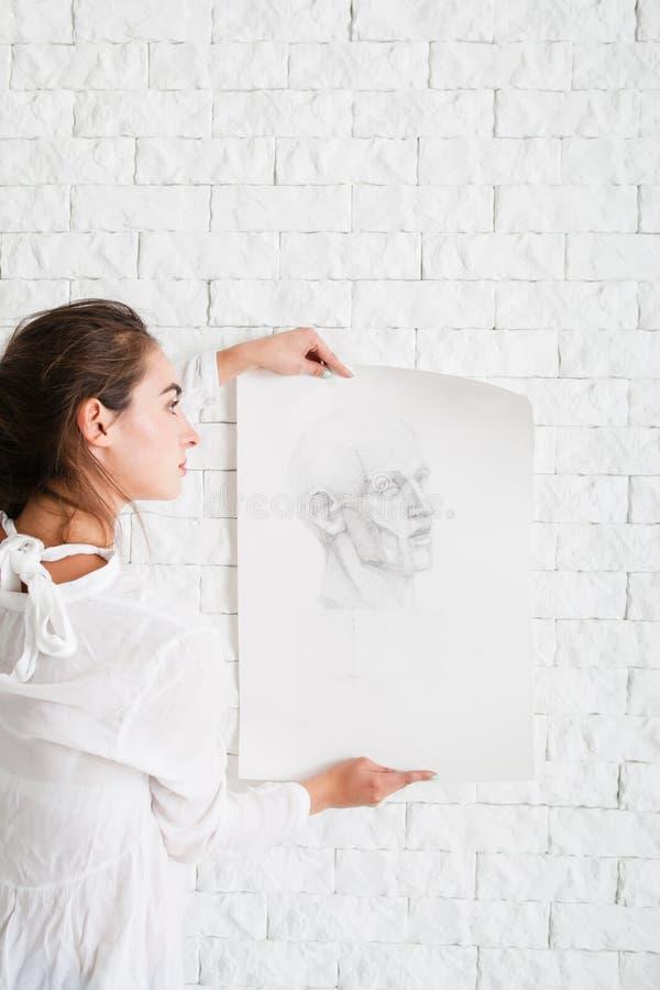 Konstnär som hänger hennes blyertspennastående på väggen royaltyfri fotografi