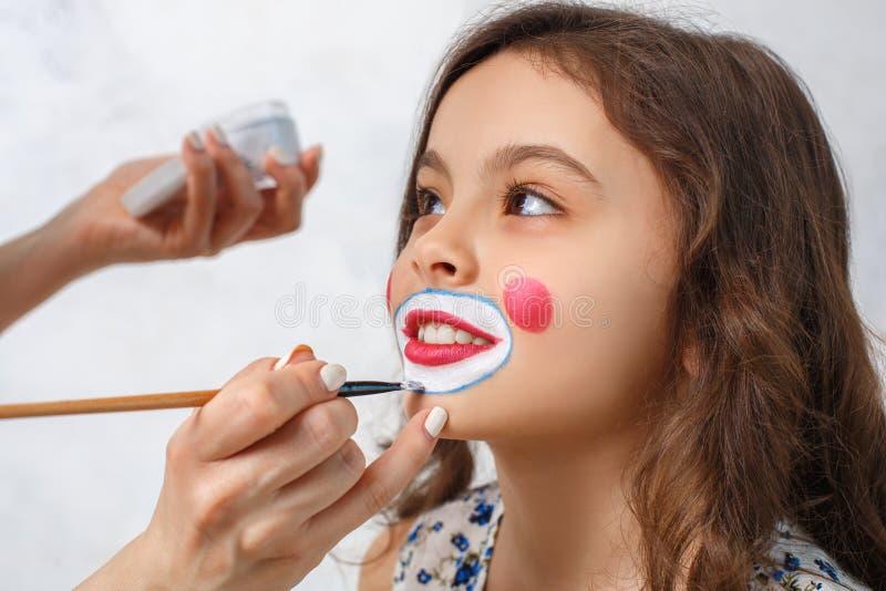 Konstnär som lite gör clownmakeup för flicka royaltyfri bild