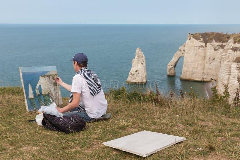 Konstnär som målar berömda elefantklippor nära Etretat i Normandie, Frankrike royaltyfri bild