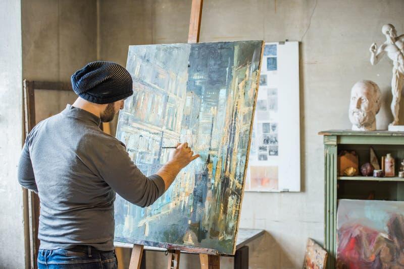 Konstnär som retuscherar ett konstverk arkivfoto