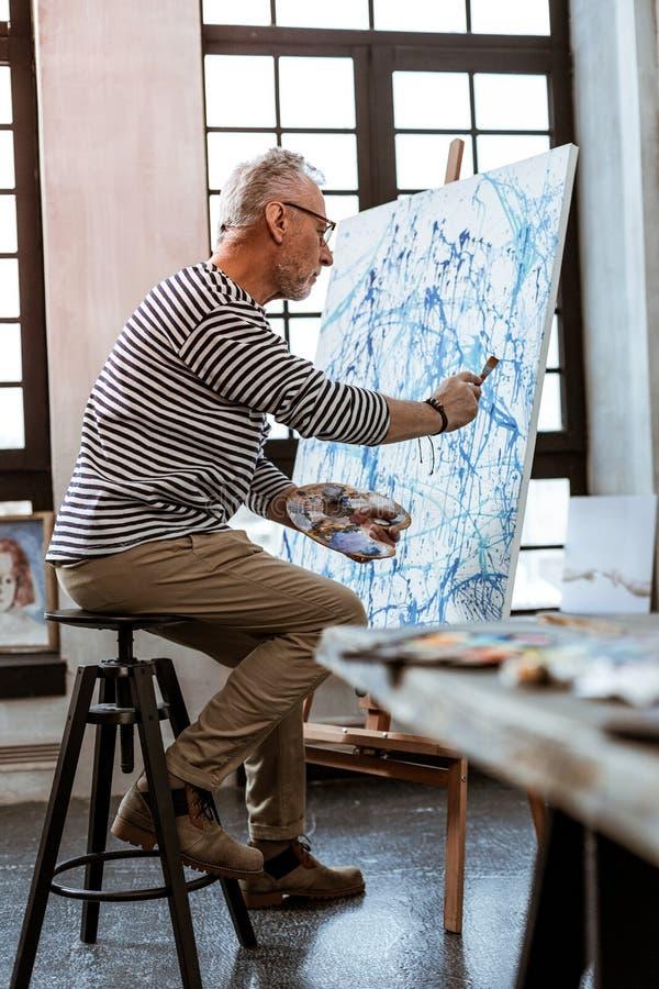 Konstnär som rymmer målningborsten, medan arbeta på ny kanfas royaltyfri fotografi