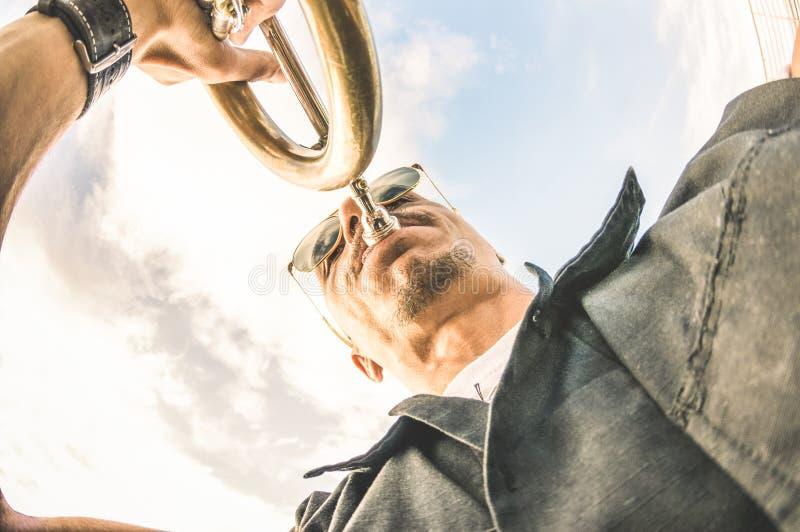 Konstnär som utför för att trumpeta solo jazz mot himmel - musik och gatakonstbegrepp på klubbaläge för öppen luft med spårlynne arkivfoton