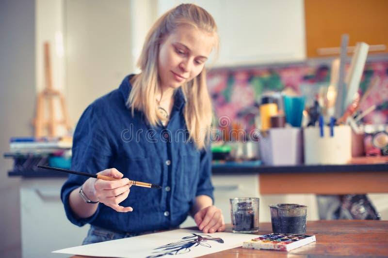 Konstnär Working On Painting för ung kvinna i studio Selektiv fokus på förgrund arkivbild