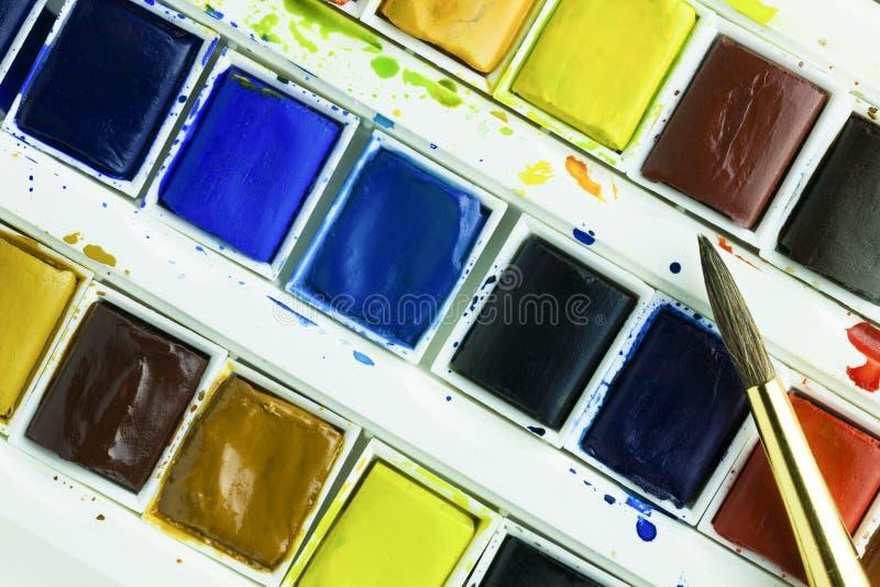 Konstnärakvarellmålarfärger och målarfärgborste royaltyfria bilder