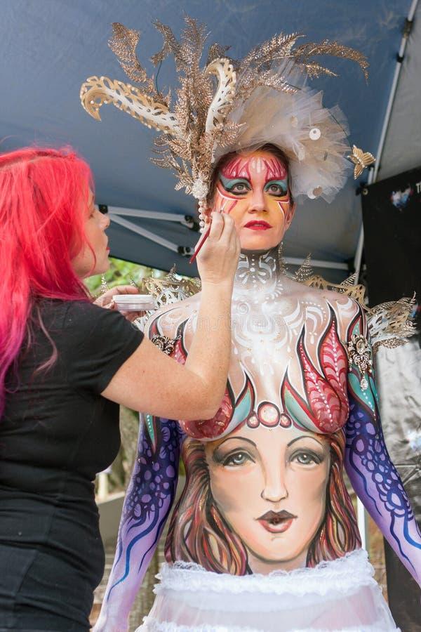 KonstnärApplies Colorful Body målarfärg till den kvinnliga modellen At Festival arkivbilder
