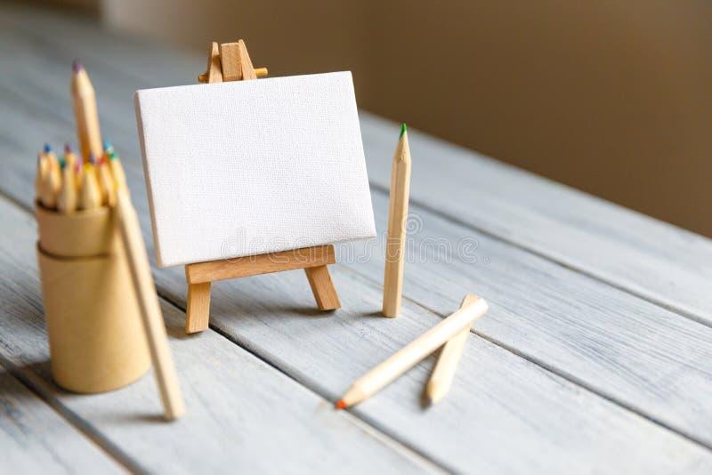 Konstnärarbetsplats: Vit tabell av en konstnär med konsthjälpmedel för att dra arkivfoton