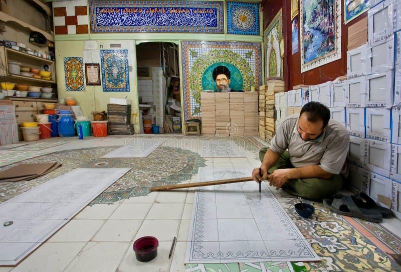 Konstnären applicerar målarfärgmodellen på tegelplattorna royaltyfri bild