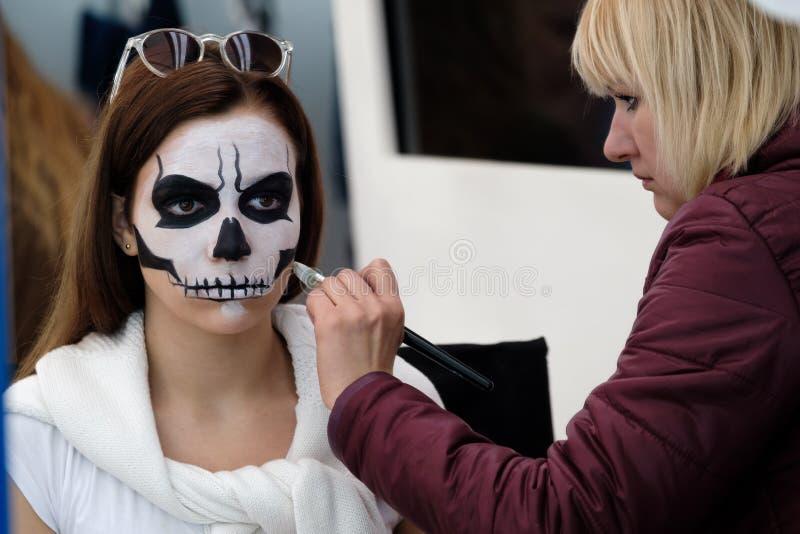 Konstnären applicerar skallesminket för gäst royaltyfri bild