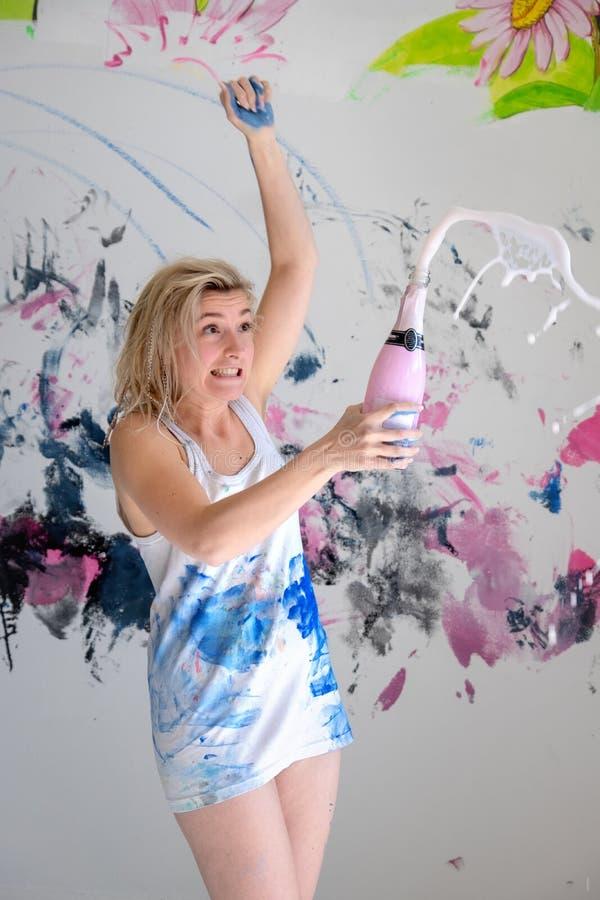 Konstnären för den unga kvinnan öppnar en mousserande flaska av champagne i färg-befläckt vit undertröja och förvånas arkivfoto