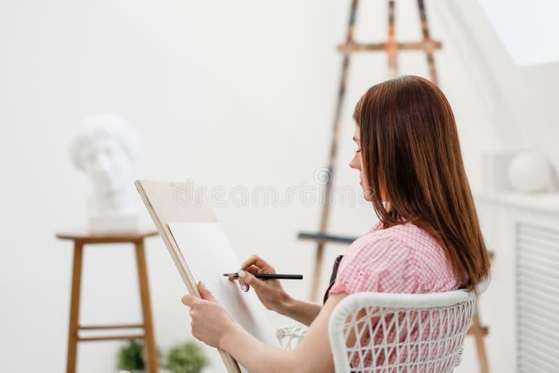 Konstnären för den unga kvinnan drar en blyertspenna på kanfas arkivbilder