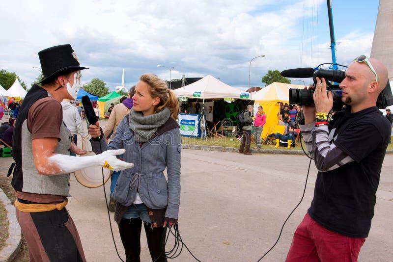 Konstnären ger en televisionintervju på festivalen royaltyfri foto