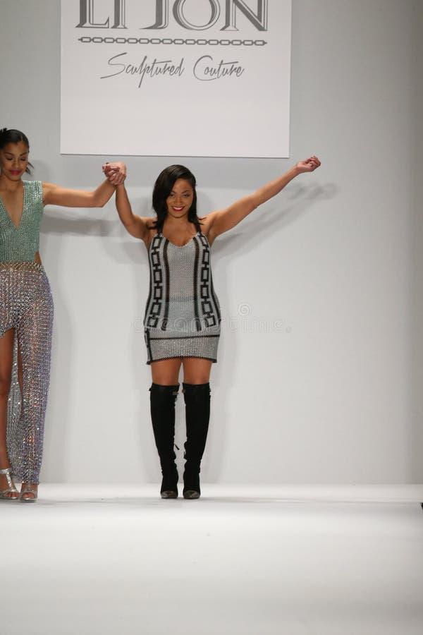 Konstnären Lia Mira (R) och modellen går landningsbanan i en Li Jon Sculptured Couture design på den Art Hearts Fashion showen arkivbild