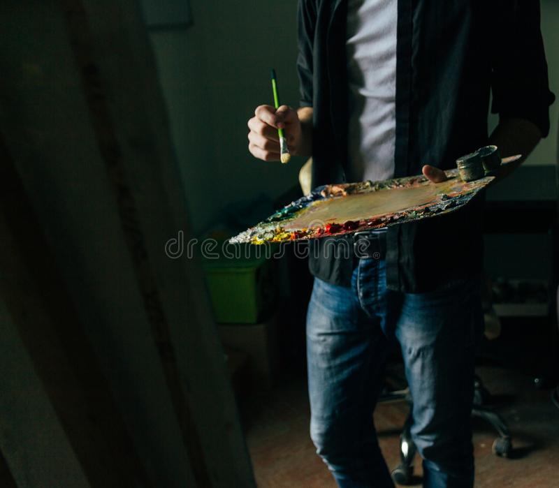 Konstnären rymmer en palett med målarfärger och en borste och ska måla på kanfas arkivfoto