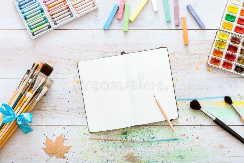 Konstnärlig idérik designworkspace, anteckningsbokåtlöje upp för konstverk med vattenfärgmålarfärger, blyertspenna, uppsättning a arkivfoto
