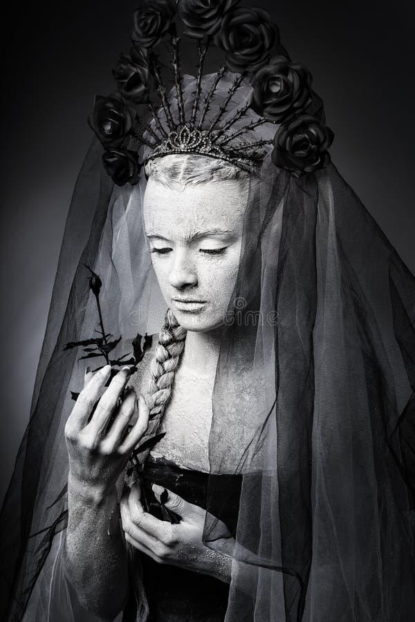 Konstnärlig porträtt av en flicka täckt av vitlackerad färg Halloween-makeup arkivfoton