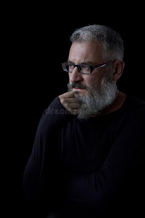 Konstnärlig stående av en brutal grå haired man med ett skägg och exponeringsglas på en svart bakgrund, selektiv fokus royaltyfri foto