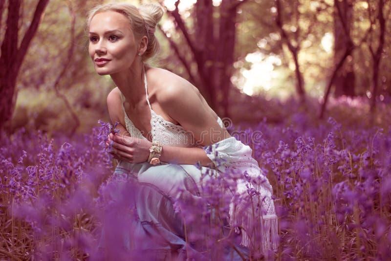 Konstnärlig stående av en flicka i en blåklockaskog royaltyfria bilder