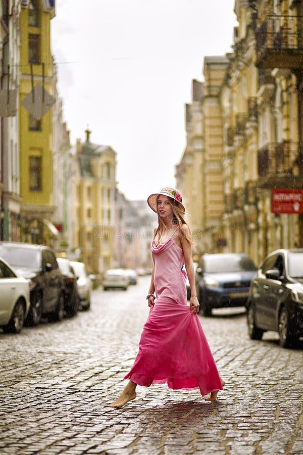 Konstnärlig stående av en ung flicka i regnet i en rosa klänning på arkivbild