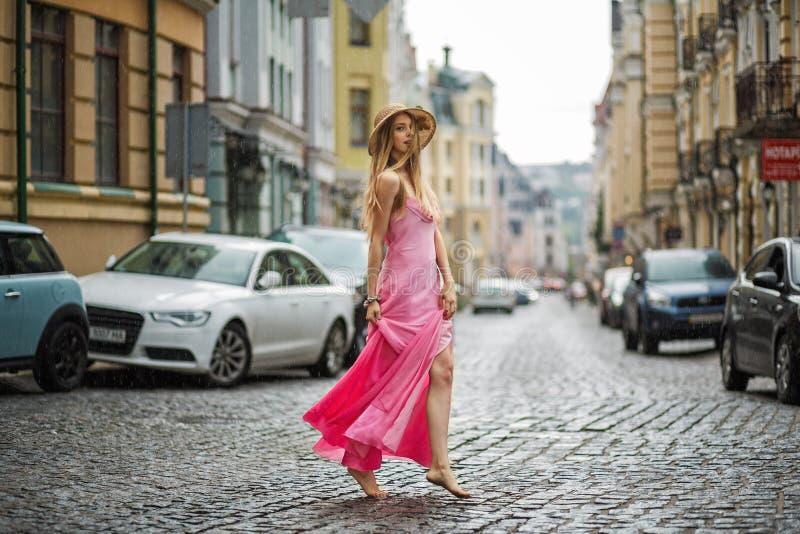 Konstnärlig stående av en ung flicka i regnet i en rosa klänning på royaltyfri fotografi