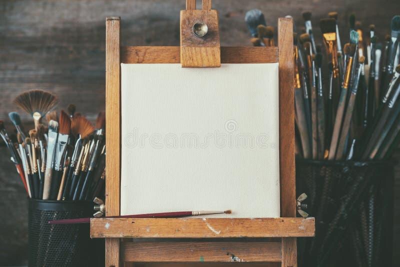 Konstnärlig utrustning i en konstnärstudio: tomma konstnärkanfas och borstar royaltyfria foton
