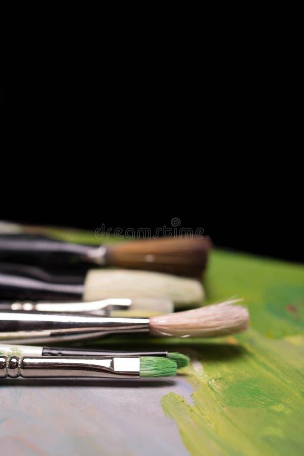 Konstnärliga borstar med spår av målarfärg på en mörk bakgrund _ royaltyfria foton
