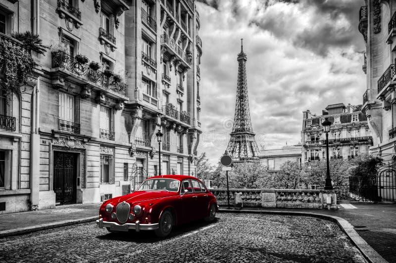 Konstnärliga Paris, Frankrike Eiffeltorn som ses från gatan med den röda retro limousinebilen fotografering för bildbyråer