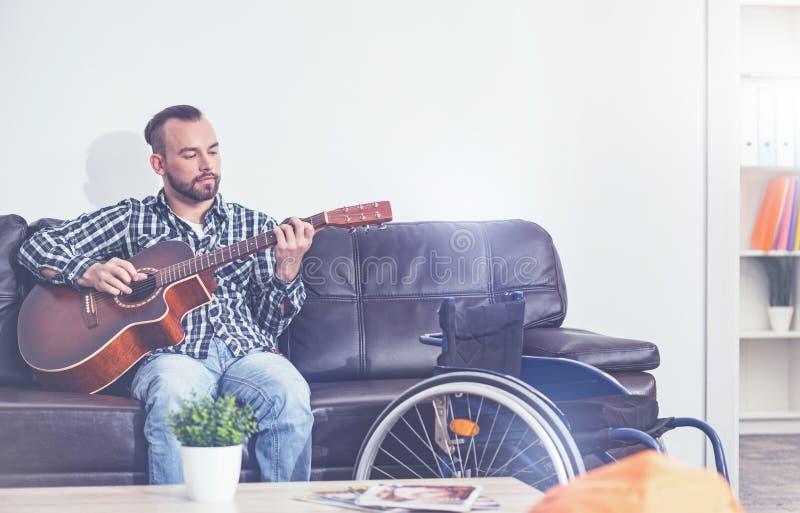 Konstnärligt ungt ogiltigt spela musikinstrument inomhus royaltyfria bilder