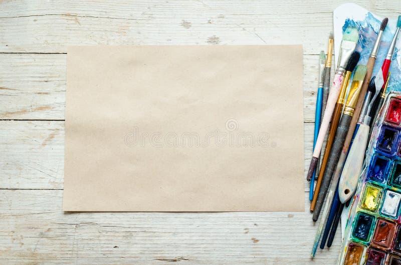Konstnärmålarfärgborstar på träbakgrunden arkivfoton