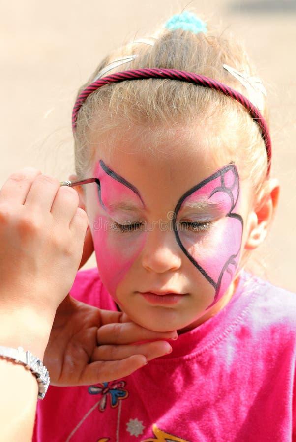 Konstnärmålarfärger på framsida av lilla flickan royaltyfria foton