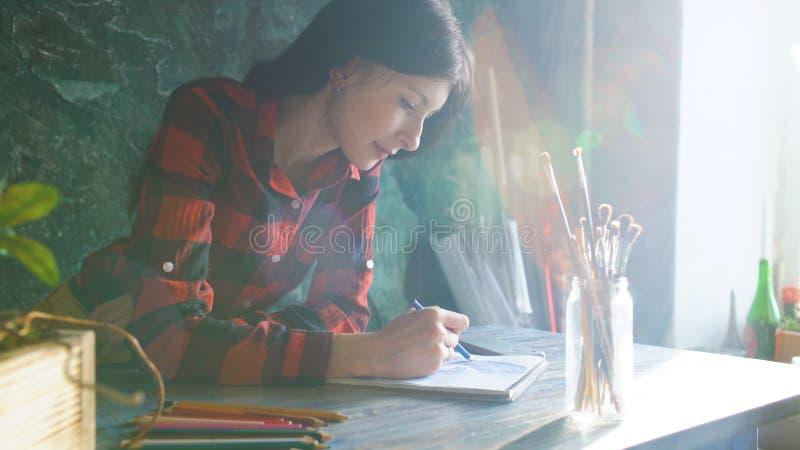 Konstnärmålning för den unga kvinnan skissar på den pappers- anteckningsboken med blyertspennan Ljus solsignalljus från fönster royaltyfria bilder