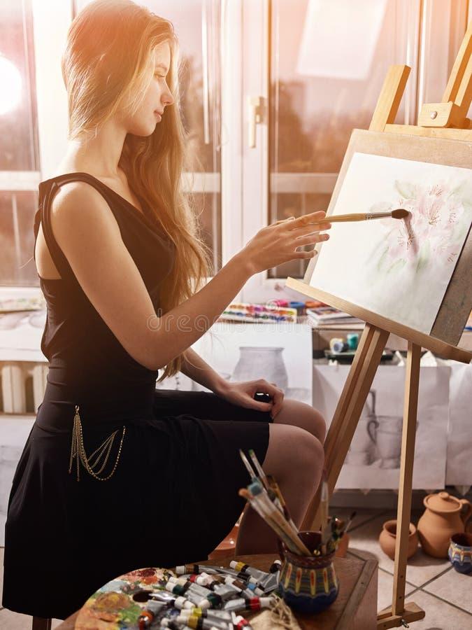 Konstnärmålning på staffli i studio Flickamålarfärger med borsten arkivbilder