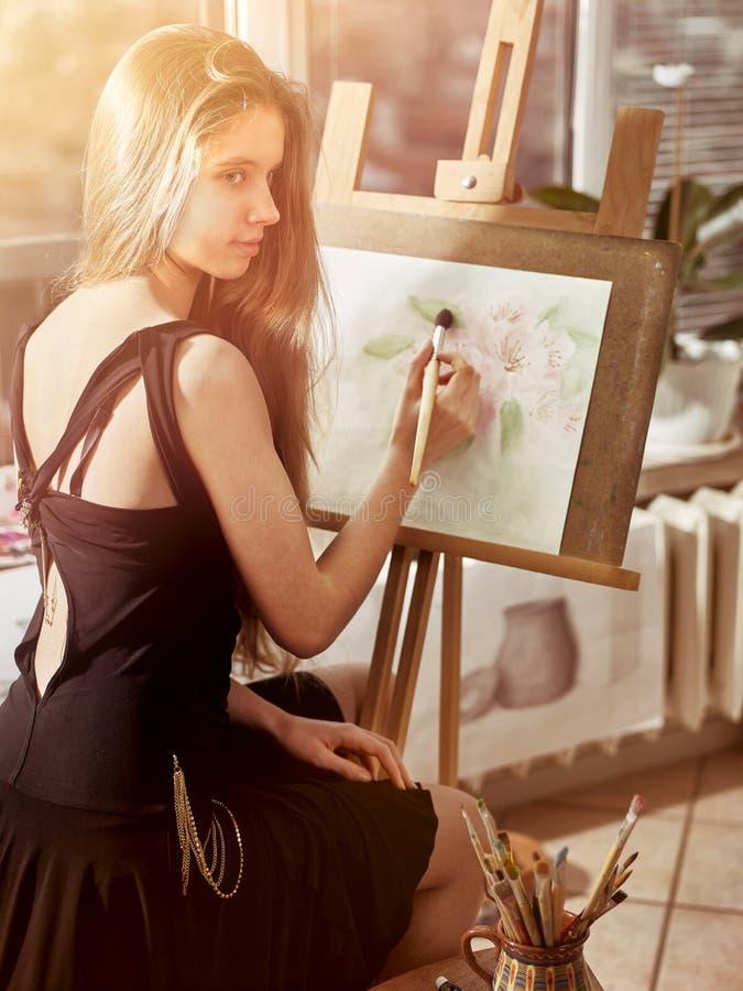 Konstnärmålning på staffli i studio Flickamålarfärger med borsten royaltyfri bild