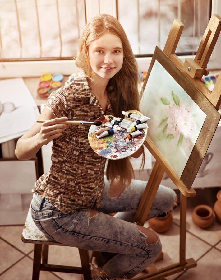 Konstnärmålning på staffli i studio Flickamålarfärger med borsten royaltyfria bilder