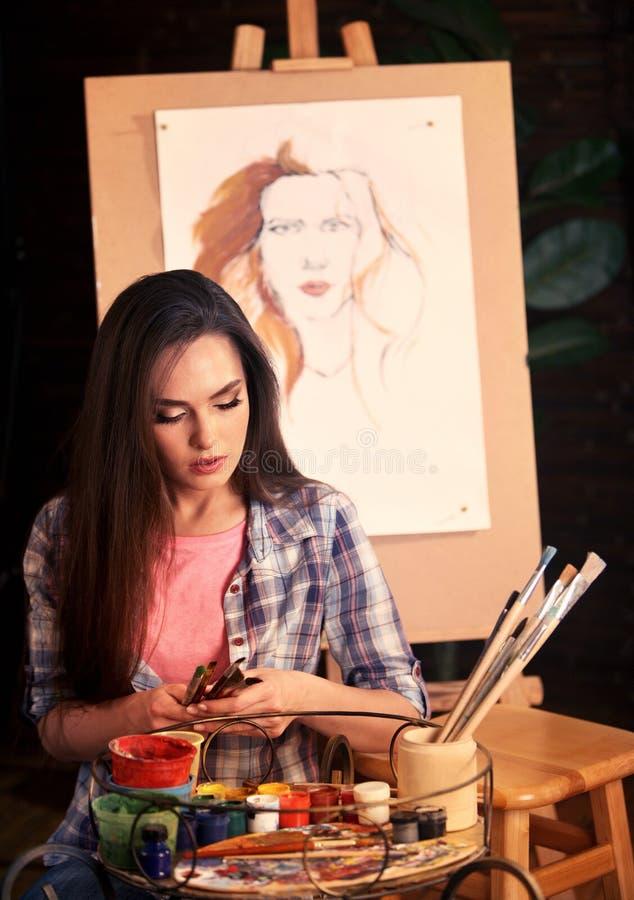 Konstnärmålning på staffli i studio Flickan målar ståenden av kvinnan med borsten arkivfoto
