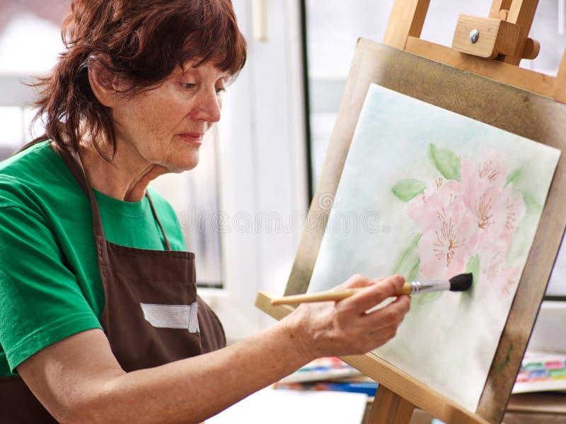 Konstnärmålningstaffli i studio Autentisk farmor och ungar royaltyfri foto