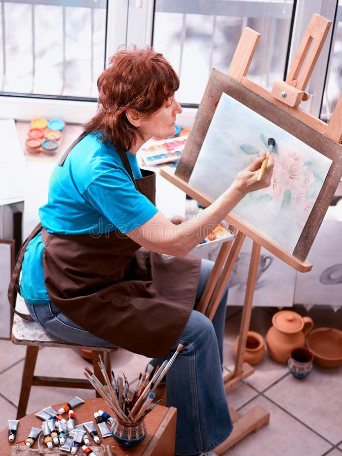 Konstnärmålningstaffli i studio Autentisk hög kvinna royaltyfri foto