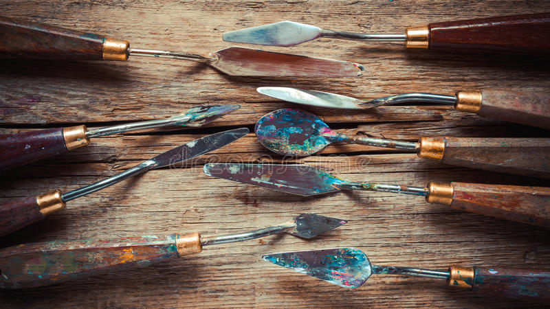Konstnärpalettknivar på den trälantliga tabellen, stiliserat retro royaltyfri bild