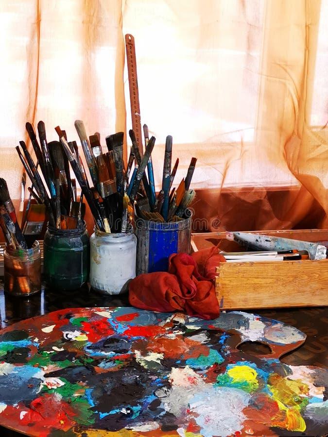 Konstnärpallete och borstar - målarehjälpmedel royaltyfri fotografi
