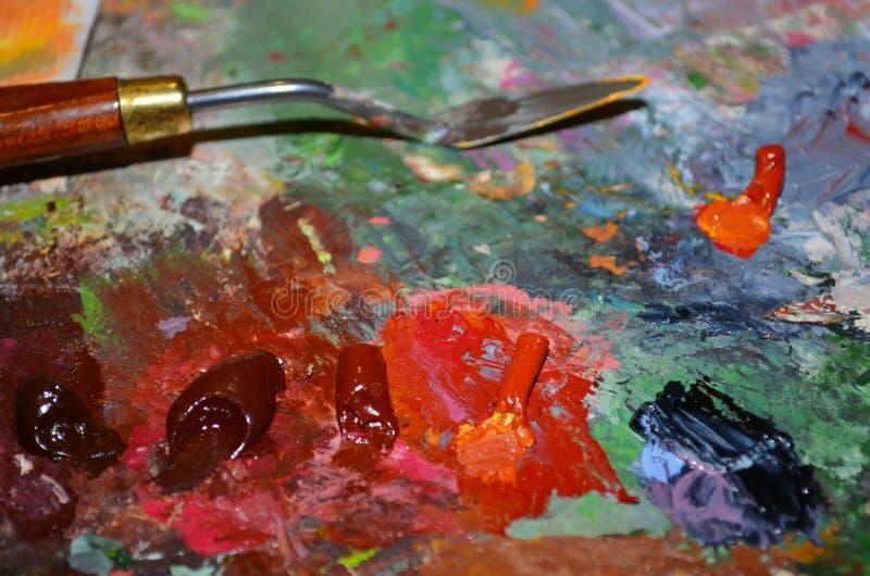 Konstnärs palett med röda målarfärger tätt upp arkivfoto