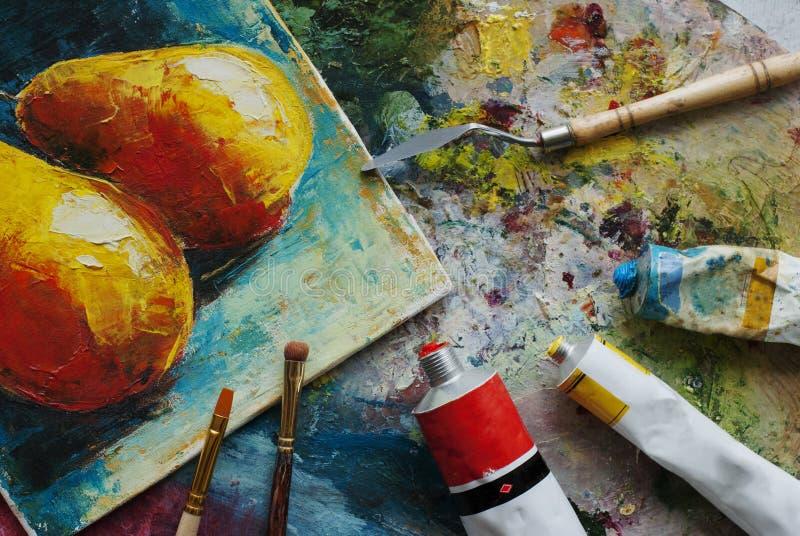 Konstnärstudio med olje- målarfärger, borstar och den färgrika bilden royaltyfria foton