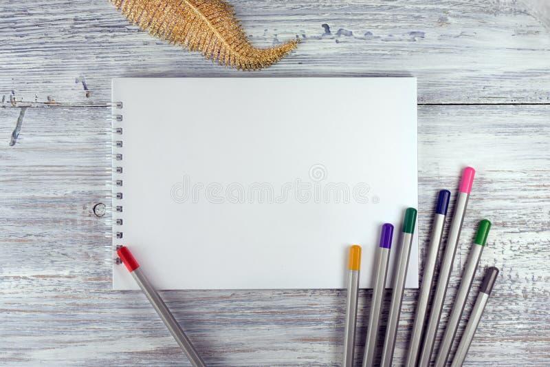 Konstnärworkspace Teckningshjälpmedel, stationära tillförsel, arbetsplats av tomt papper för konstnär på det vita träskrivbordet, royaltyfria bilder