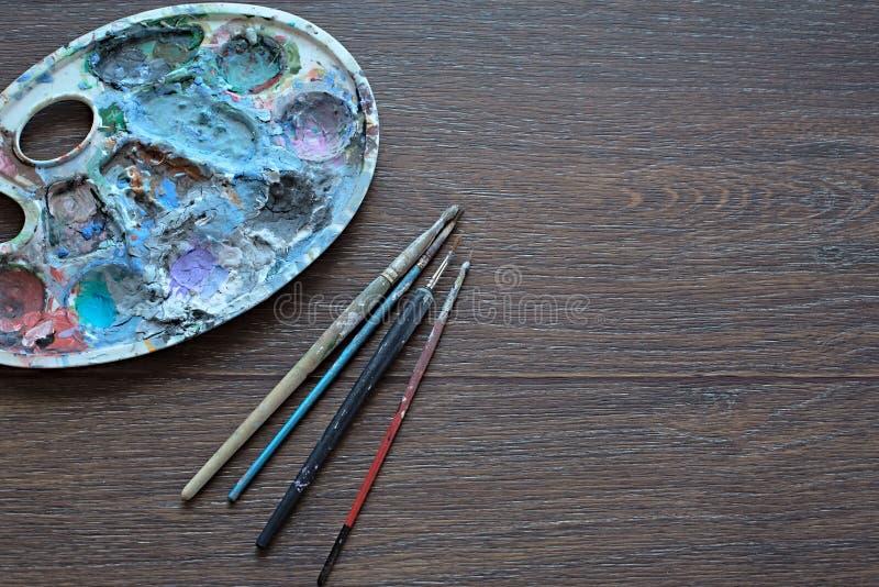 Konstpalett och borstar för att måla på träbakgrund övre sikt royaltyfri foto