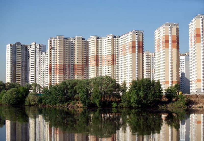 Konstruerat flerbostadshus över blå himmel för flod och för frikänd i sommardag royaltyfri fotografi